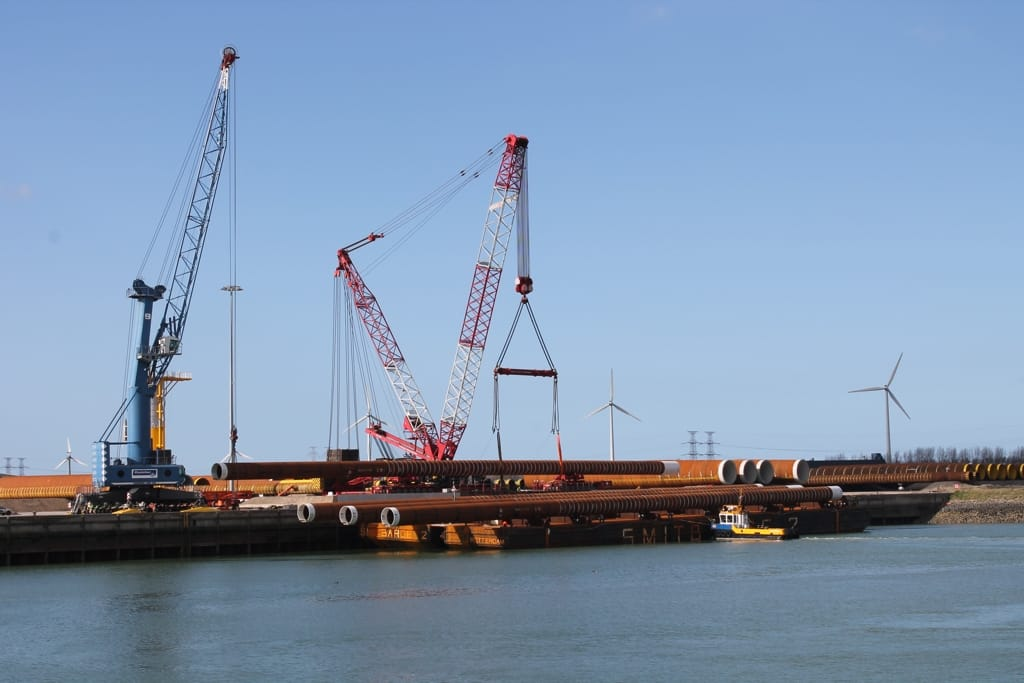 Vessel carrying pipes. Crane loading pipes.